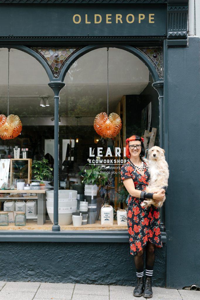 Olderope shop owner holding dog